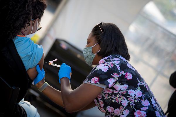 UC San Diego Health staff administers a COVID-19 vaccination at a UC San Diego Health mobile vaccine clinic.